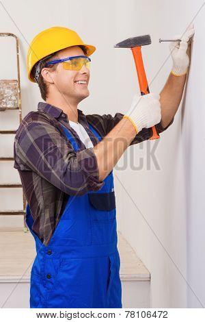 Handsome repairman nailing