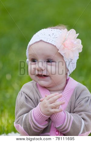 Little elegant girl against a summer green grass