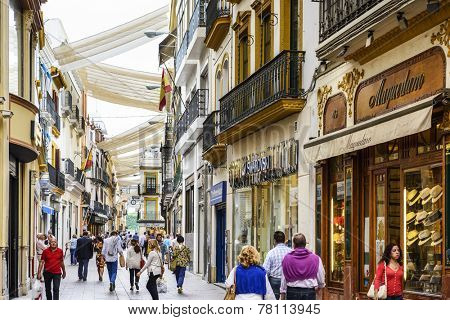 SEVILLE, SPAIN - CIRCA 2014: Shoppers stroll through Calle Sierpes. The street is considered the prime shopping district of the city.