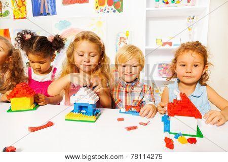 Nice little kids play with plastic blocks