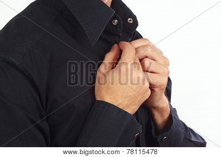 Man fastened the buttons of collar on the black shirt closeup