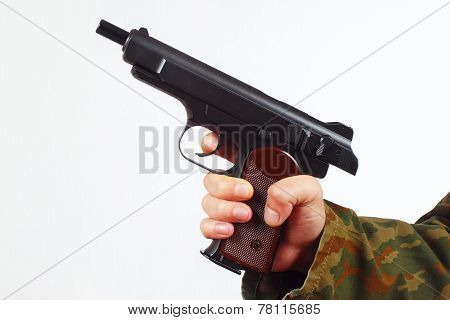 Hand in camouflage uniform with discharged gun on white background