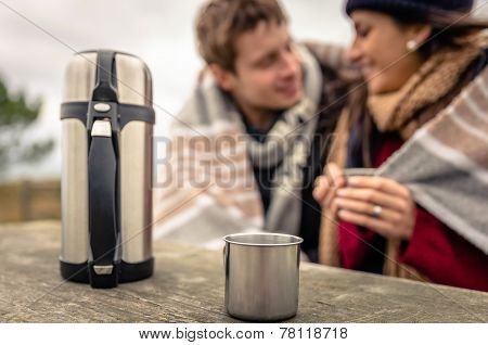 Metalic cup and thermos outdoors with couple blurred on background