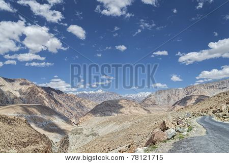 Remote Winding Road Among High Snow Capped Mountains