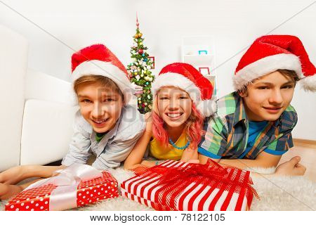 Happy teen kids with Santa hats and smiles