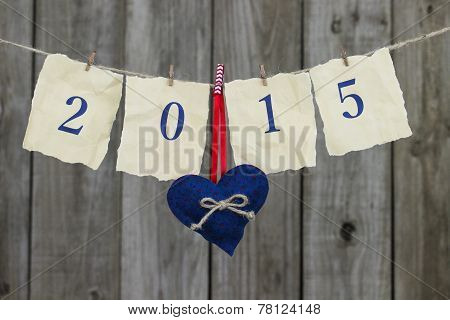 Year 2015 in blue on antique parchment paper hanging on clothesline with red, white and blue heart