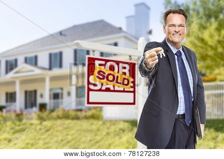 Real Estate Agent with House Keys in Front of Sold Sign and Home.
