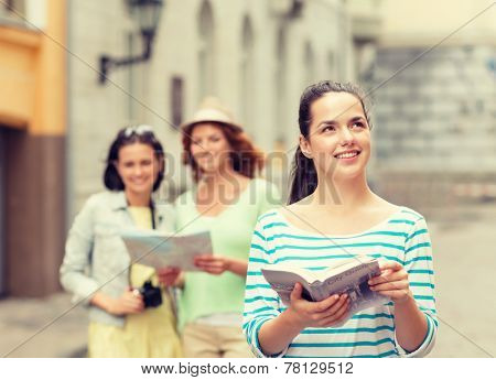 tourism, travel, holidays and friendship concept  - smiling teenage girls with city guide, map and camera outdoors