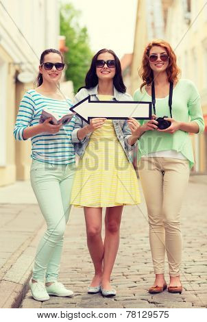 tourism, travel, vacation, direction and friendship concept - smiling teenage girls with white arrow showing direction outdoors