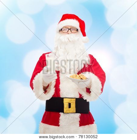 christmas, holidays, food, drink and people concept - man in costume of santa claus with glass of milk and cookies over blue lights background