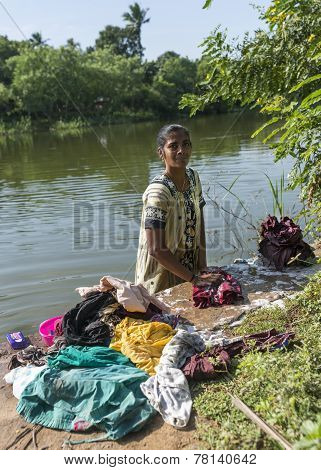 Woman Does The Laundry Standing In The River.