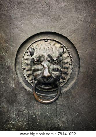 Antique Door Knocker In The Form Of A Lion's Head On Old Metal Door