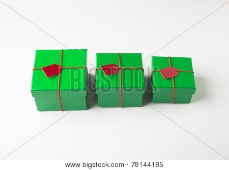 Group of various sizes green color gift boxes arranged in a row.