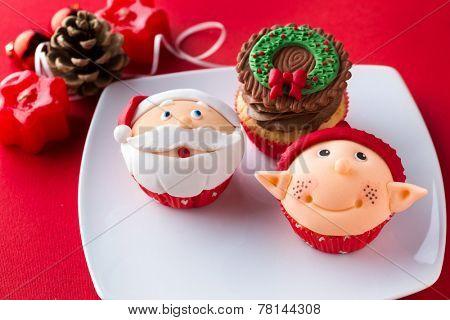 Three decorative Christmas cupcakes  on white plate