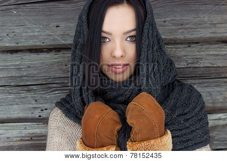 beautiful woman with black hair in mittens stands near the wooden wall in winter