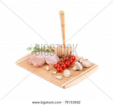 Raw chicken breast on the wooden board.