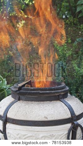 Flames leap out of the tandoor.