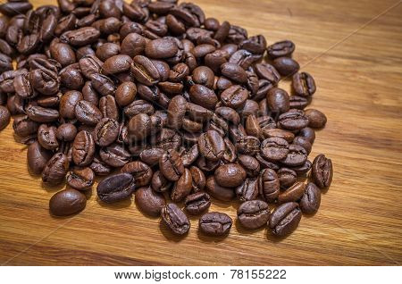 Arabica coffee beans spilled on table background