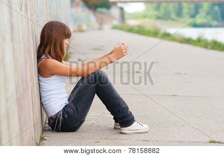 Cute lonely teenage girl sitting in urban environment