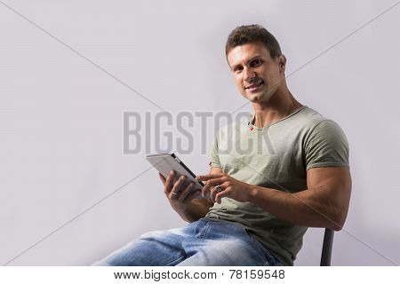 Muscular Young Man Sitting On Chair Reading From Ebook Device