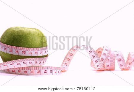A green apple and a measurement tape, isolated on white