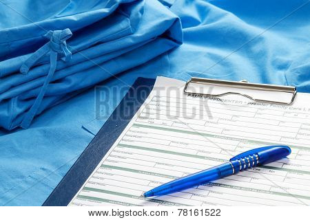 A clipboard and a pen on a medical uniform, closeup
