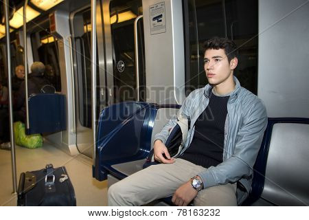 Young Man Sitting In Subway Train Commuting To Work