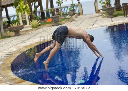 Man tries to jump in water in swimming-pool