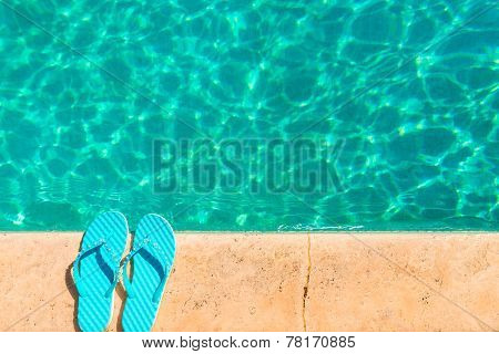Turquoise Flip Flops At The Edge Of The Pool