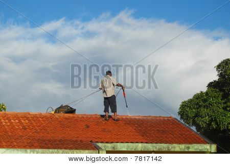 Man in Mauritius cleaning the roof