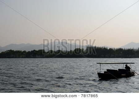 Silhouette Of Man Rowing Boat Against Scenic Mountains