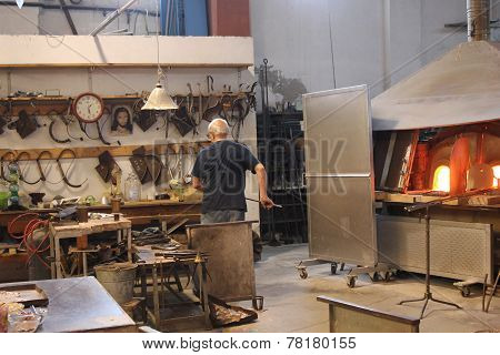 An Artisan At Work in its furnace