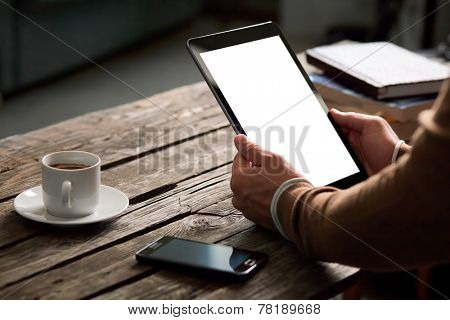 Tablet computer with isolated screen in male hands over cafe background - table, smart phone, cup of coffee...