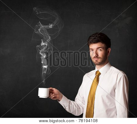 Businessman standing and holding a white steamy cup on a black background