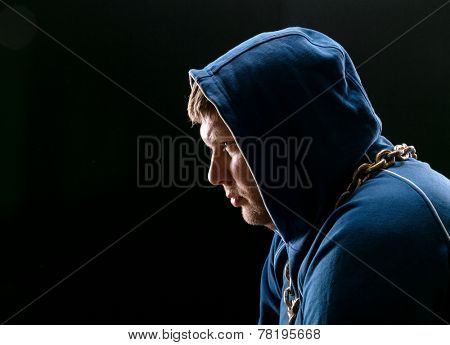 Angry man, sitting with hood on