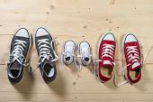 picture of daughter  - three pair of shoes in father big mother medium and son or daughter small kid size representing family growth education and togetherness concept - JPG
