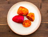 picture of prickly pears  - Prickly pear cut on plate on wooden table seen from above - JPG