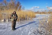 foto of hunter  - Hunter on the ice pond waiting victim - JPG
