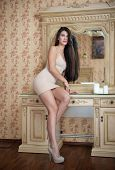 stock photo of nearly nude  - Charming young brunette woman in tight fit short nude dress in front of a mirror - JPG