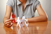picture of hiv  - Female hands holding paper people and a red hiv ribbon - JPG