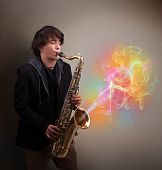 foto of fumes  - Attractive young musician playing on saxophone with colorful abstract fume comming out - JPG