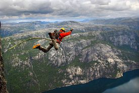 picture of roping  - Man jumping off a cliff with a rope - JPG