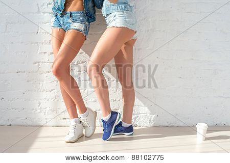 sporty long sexy legs of two beautiful women jeans shorts urban casual street style fashion sunny da