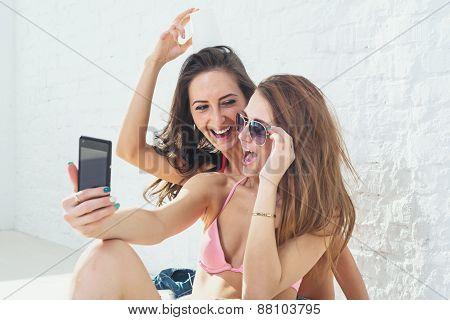Female friends laughing having fun taking selfie together wearing bikini bra swimsuit summer sunny d