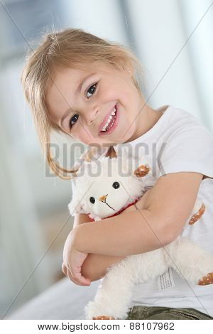 Portrait of cute blond little girl hugging teddy