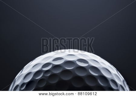 Stylish golf ball isolated on empty dark blue background, close up shot with  blank space for text.