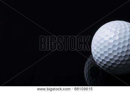 Close up of golf ball lying on black surface with reflection, isolated, copy space for text.