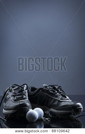 Golf equipment consisting of balls, tees and shoes, isolated on dark blue background with empty copy space for text.