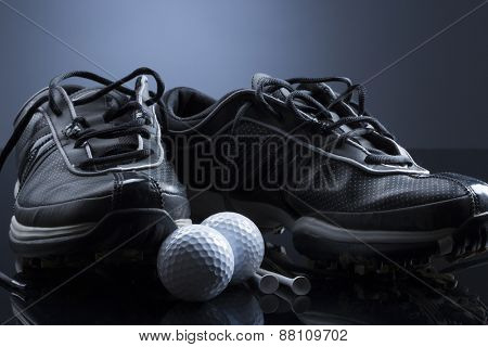 Golf equipment consisting of balls, tees and shoes, isolated on dark blue background.