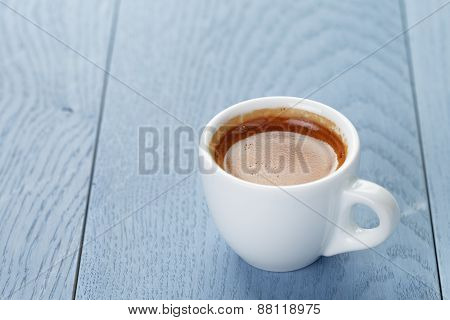 cup of fresh espresso on vintage blue table